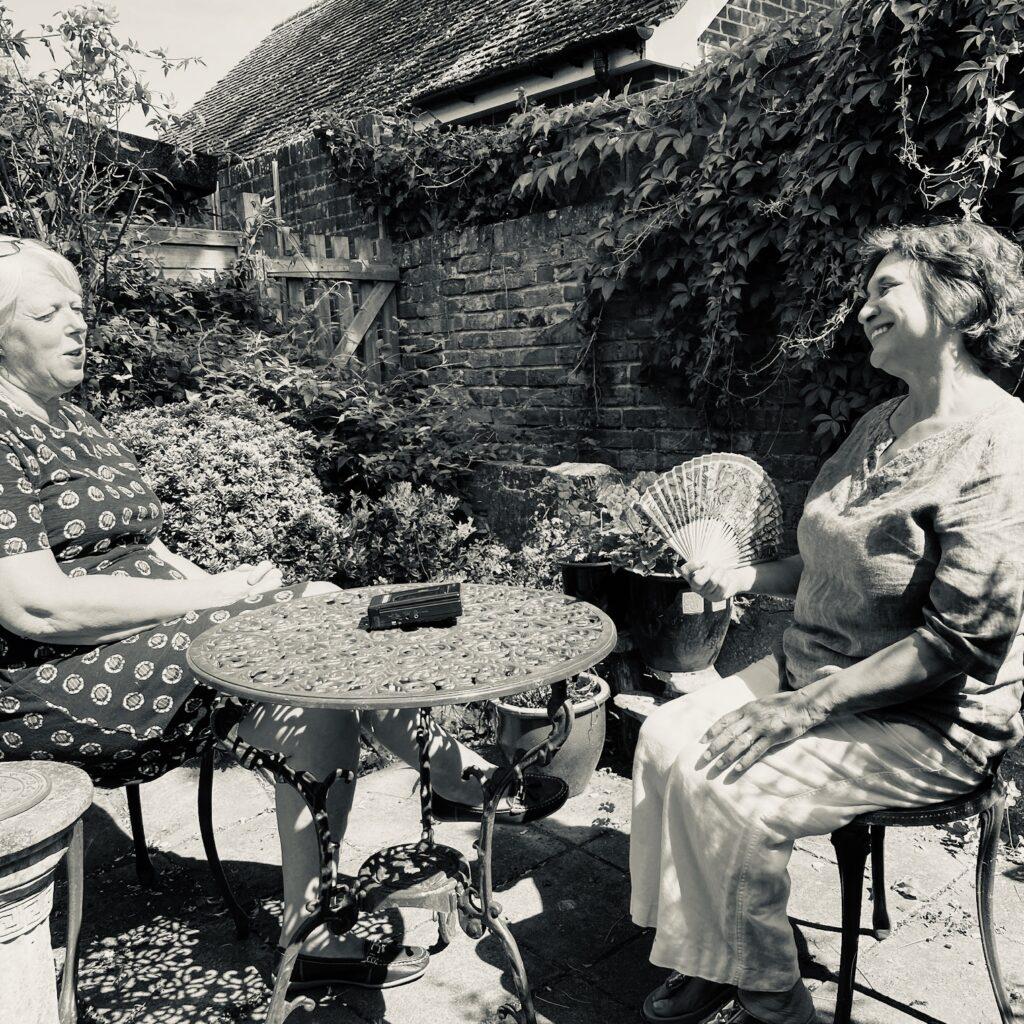 contemporary women being interviewed in the garden socially distanced