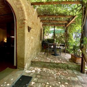 Table under the vines outside guest accommodation in Volterra