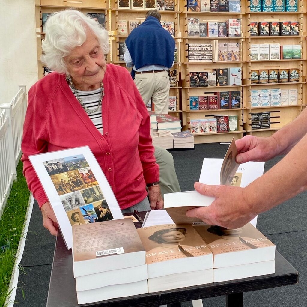 Eve signing a book for a visitor at the ChalkeValley History Festival in the Waterstones Tent